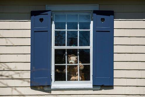 A stuffed bear is visible through a window