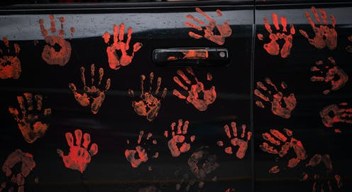 Handprints representing 215 Indigenous childrenare seen on the side of a truck.