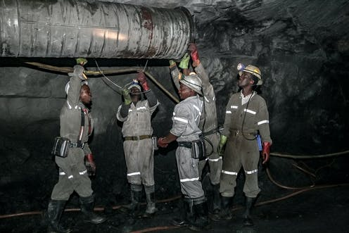 Men in helmets, overalls, boots and gloves stand in a tunnel underneath a large pipe