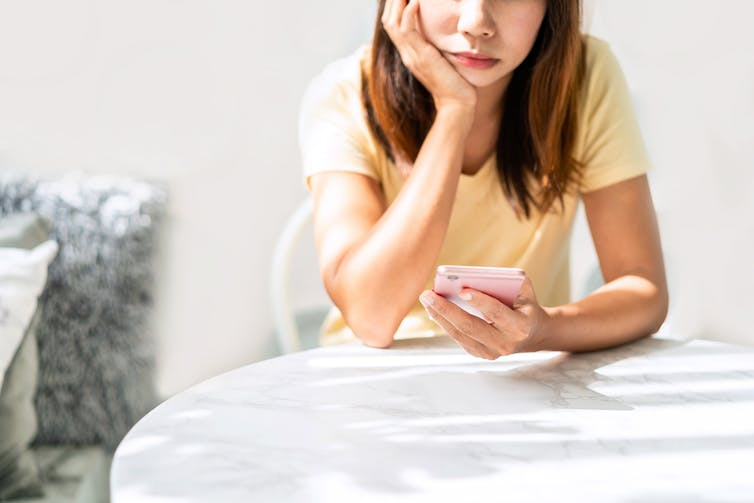 Woman looking bored on her phone.