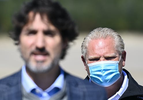 Doug Ford, wearing a mask, is seen behind Justin Trudeau.