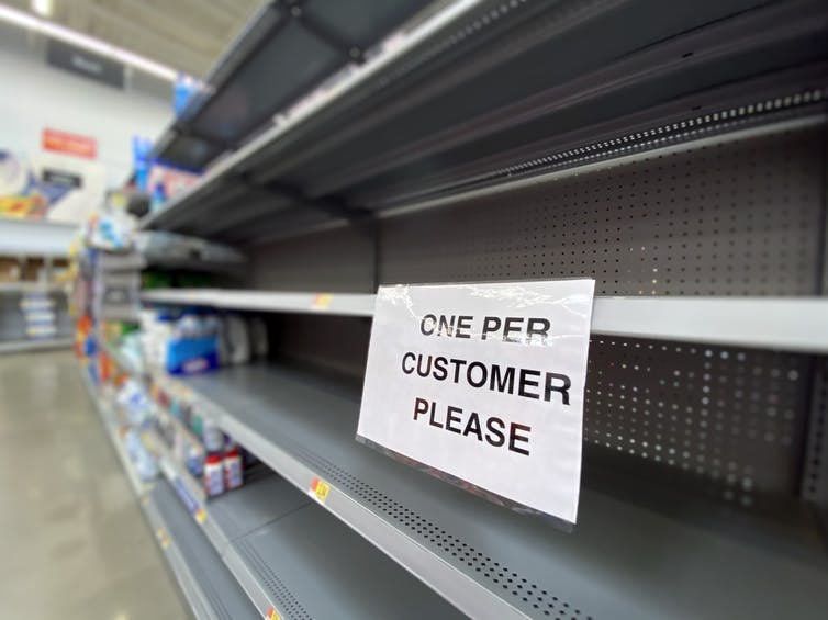Empty supermarket shelf with 'one per customer' sign