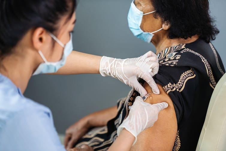 Woman doctor giving older Indian woman a vaccine shot into the shoulder