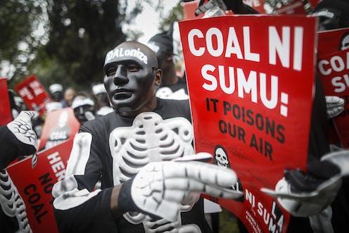 Man in skeleton outfit holds sign saying 'Coal ni sumu'