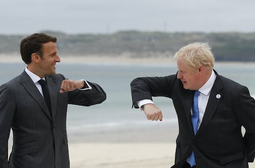 French President Emmanuel Macron and British Prime Minister Boris Johnson hold out their arms with their elbows pointing toward each other as they prepare for an elbow bump during a G-7 meeting