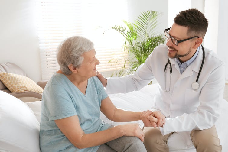A male doctor consulting with an older female patient