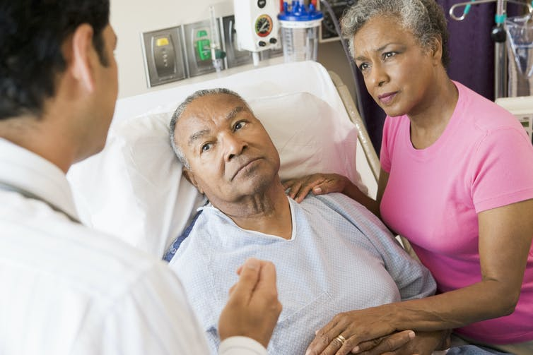 A man in a hospital bed and a woman holding his hand, listening to a doctor whose back is to the camera.