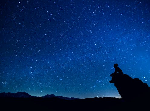 A person sits on a rock promontory against a vast night sky full of stars.