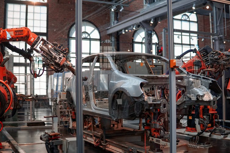 Robotic arms reach into the frame of a car being manufactured