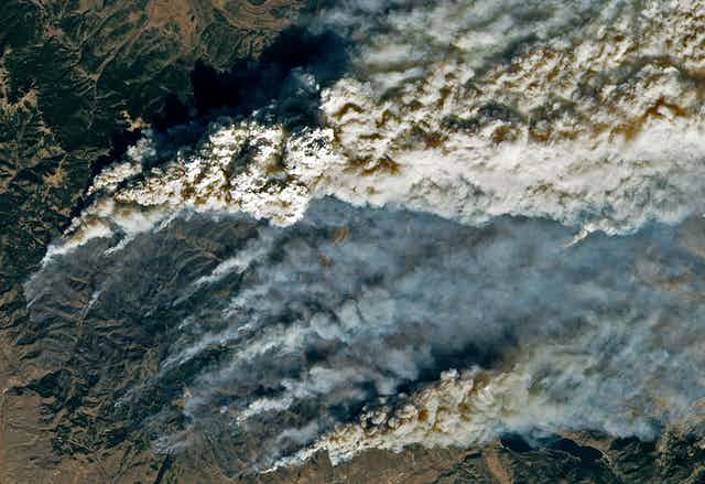 A satellite image shows smoke trailing up from multiple hotspots on the fire line in the mountains.