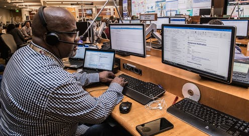 A man with headphones on with three computer screens in front of him.