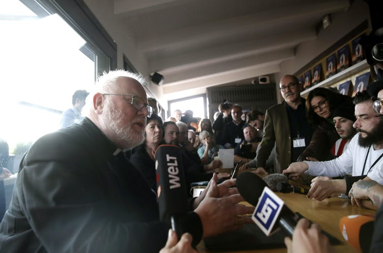 A man in a priest's collar and with a beard speaks with some reporters and a crowd.