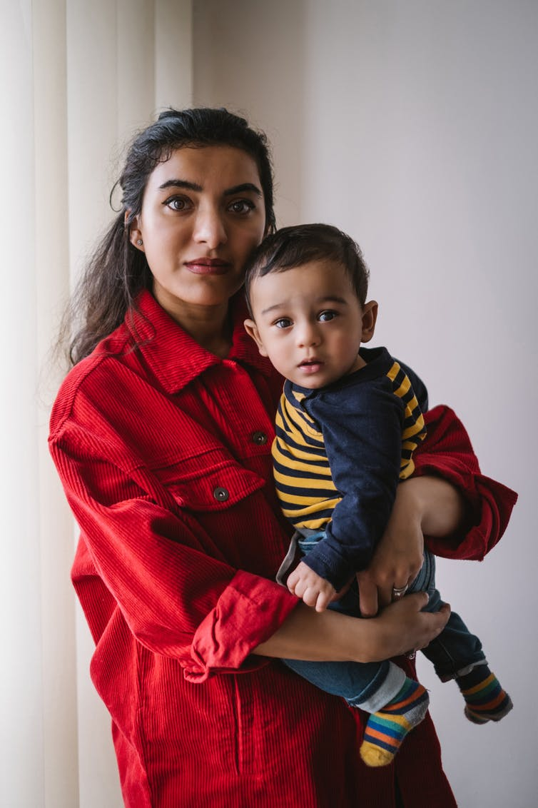 Pakistani woman in red shirt holding her son