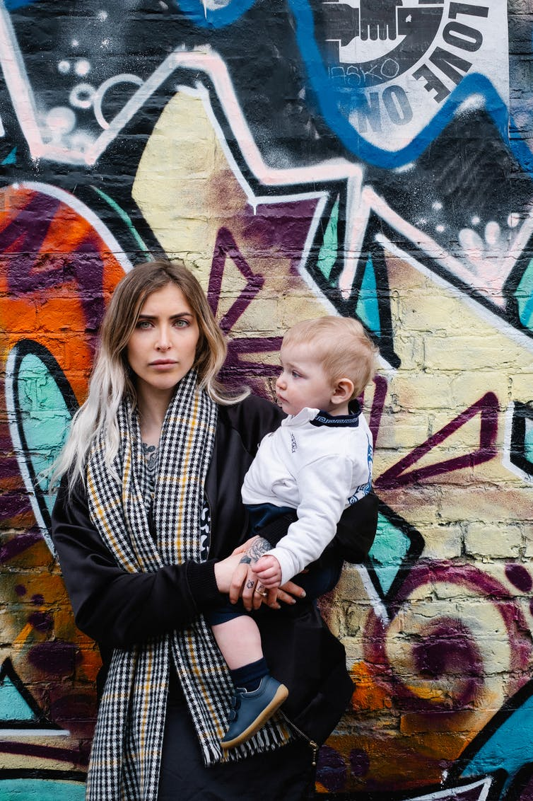 Woman holding her son and standing in front of graffiti