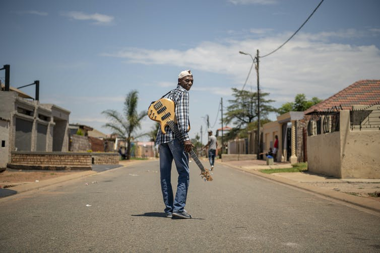 A township street and a blue sky; an elder man stands in the middle of the road and looks back to the camera, a guitar slung over his shoulder.