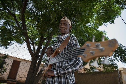 Beneath a tree, an elder man in a chequered shirt holds a guitar, looks wryly ahead.