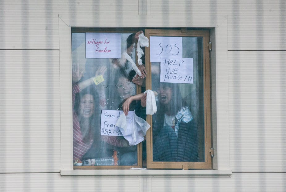 Detainees in Yarl's Wood Immigration Removal Centre hold up signs calling for help reading 'hunger for freedom', 'SOS' and 'help we please'