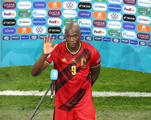 Striker Romelu Lukaku of Belgium speaking to the press in front of an advertisement screen