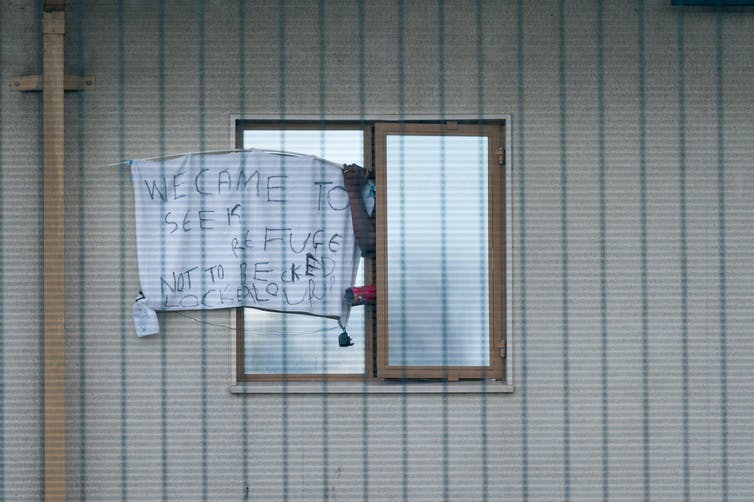 Window with a sign on it reading  'we came to seek refuge, not to be locked up' outside Yarl's Wood Immigration Removal Centre