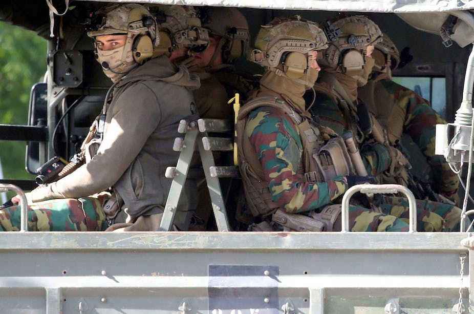 Belgian soldiers in full gear sitting in the back of a truck.