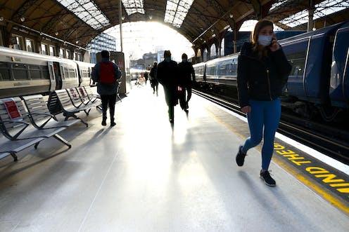 Passengers walk along the platform in Victoria rail station, London