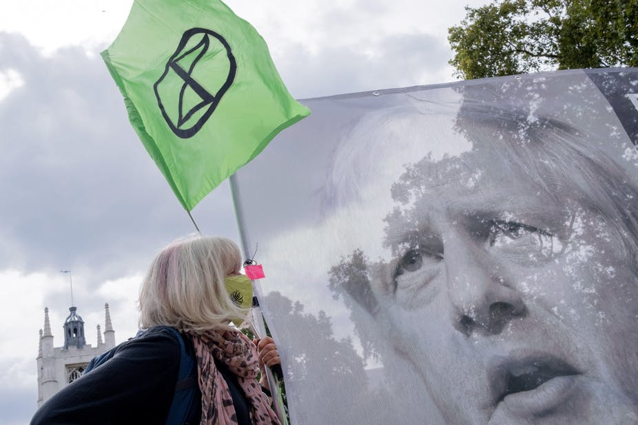 Climate change protester with a banner of Boris Johnson