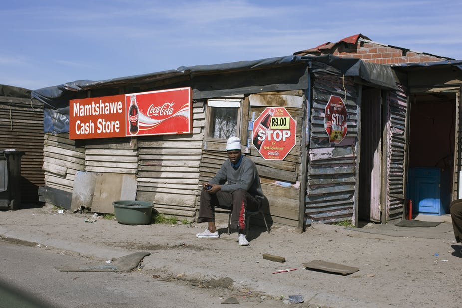 A young man sits outside an informally built structure with commercial signage