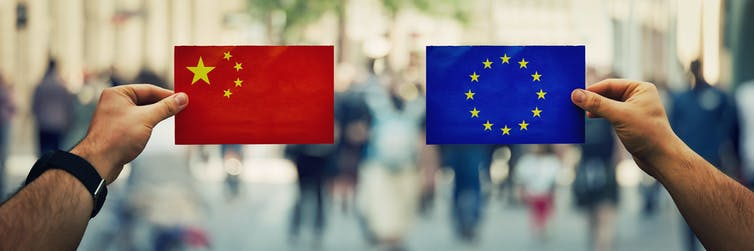 Hands holding up flags of China and EU