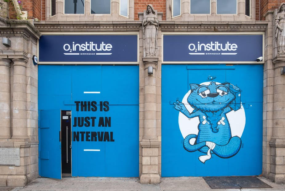 O2 Institute building with the words 'this is just an interval' painted in black against a blue door and on the door to the right, a painting of a bandaged blue cat carrying a boombox next to its head