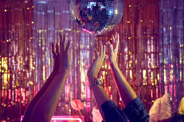 Hands in the air in a club reach upwards towards a discoball in front of a metallic fringe curtain