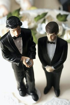 Statuettes of two men in tuxedos adorn the top of a wedding cake.