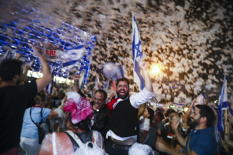 People smile and celebrate in a crowd, waving Israeli flags