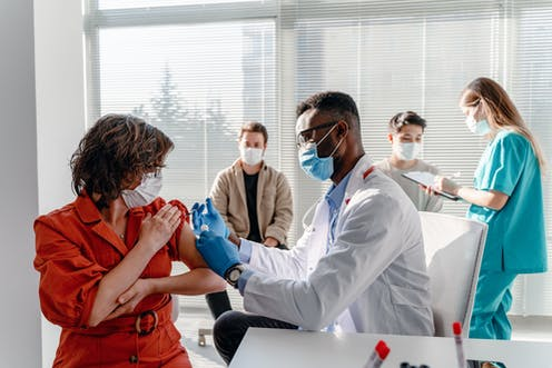 Person getting vaccinated in a clinic with two other people getting checked in.