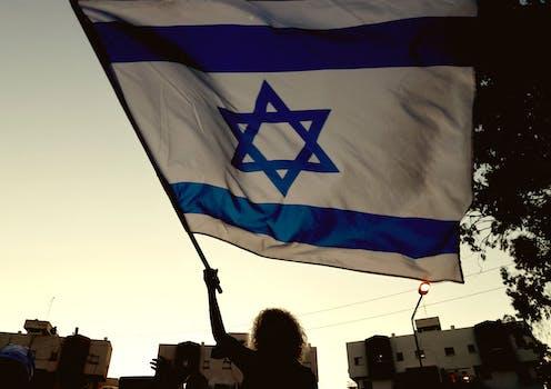Woman waves an Israeli flag at dusk