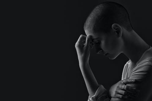 Mujer con el pelo rapado, de perfil, en blanco y negro.