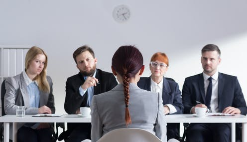 A woman is seen from behind sitting on a chair facing a panel of four other people during an interview.