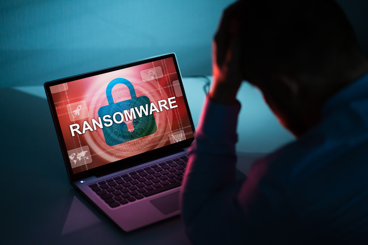 shadow of a man with his head in his hands looking at a laptop screen that says RANSOMWARE