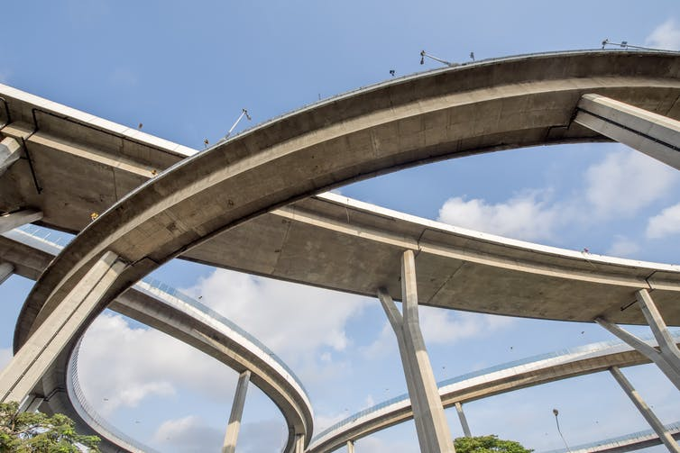 Looking up at a tangle of highway overpasses.