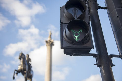 A traffic light altered so the green light flashes the symbol of gender diversity.