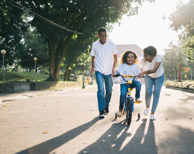 Family of three, mother and father push child on bike with training wheels down tree lined street.