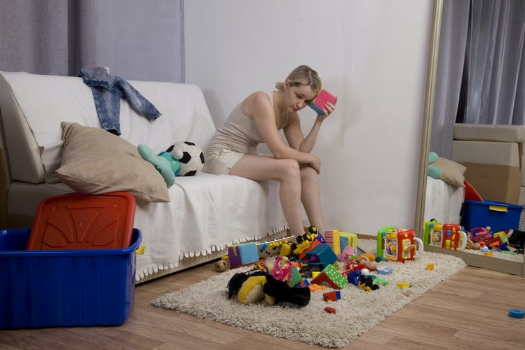 Woman sits on couch looking at a messy nursery as she places toy on to her head in frustration