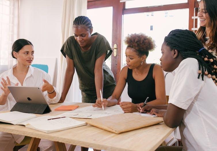 Five women at a desk have a conversation.