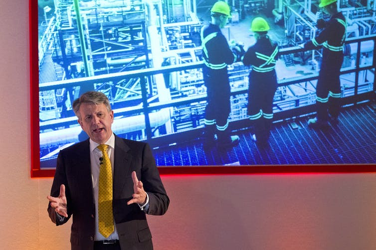 Shell's CEO speaking in front of a photo of fossil fuel workers