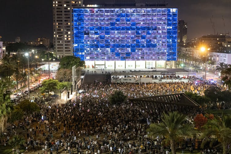Thousands of people dancing in a public square in Tel Aviv, Israel.