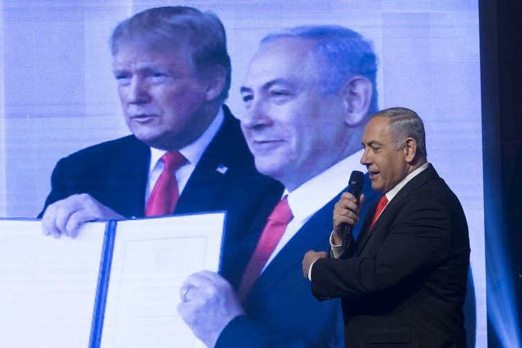 Benjamin Netanyahu stands in front of a large photo showing him and U.S. President Donald Trump.
