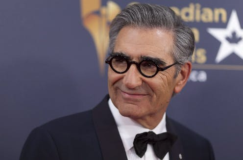 A man in round glasses and a black bowtie smiling.