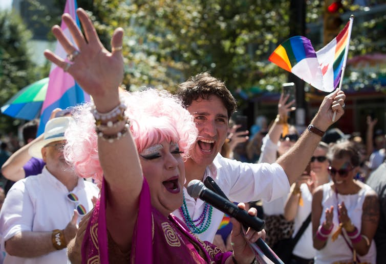 Justin Trudeau stands behind a drag queen during a Pride parade