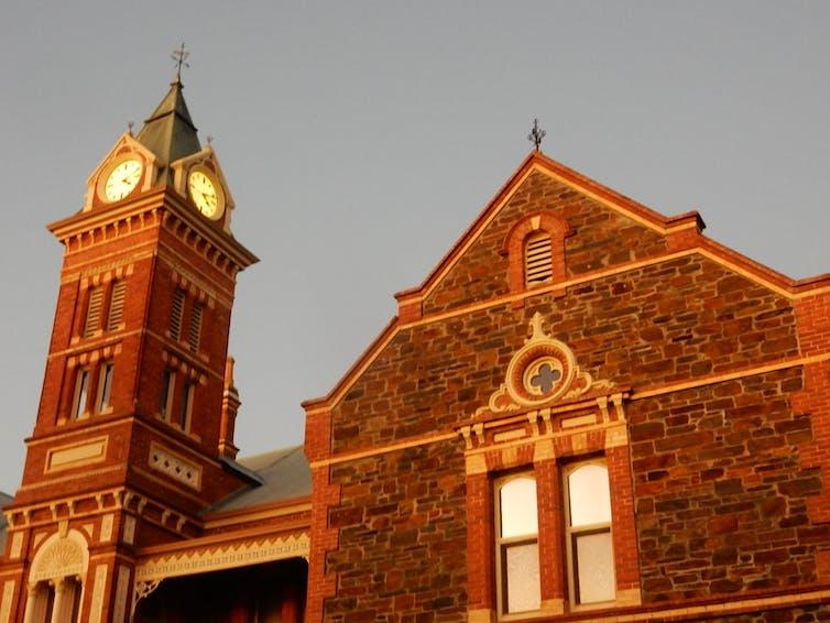 View of clocktower of bluestone building at sunset.