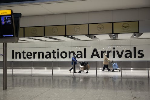 Two people walking through airport in front of sign saying 'international arrivals'