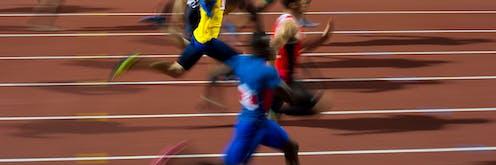blurred sprinters on running track